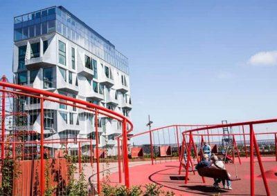 rød legeplads med bygning i baggrunden