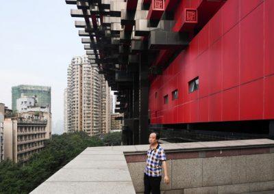 en mand står på balkon og kigger udover byen