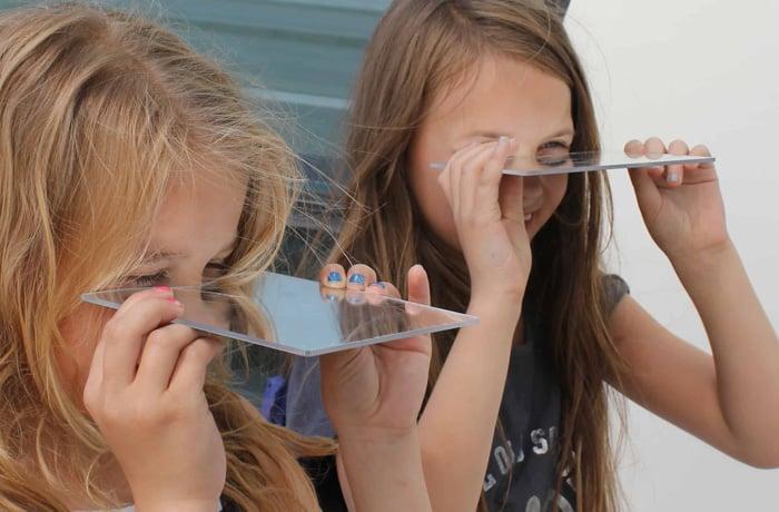 to piger der kigger gennem en glasplade