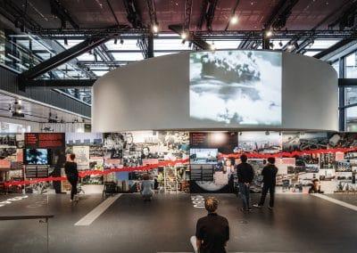 Mand sidder og kigger på udstilling med billeder og film